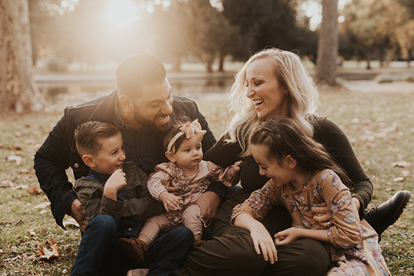Portrait of Justin Ingolia with his wife and children in a park.