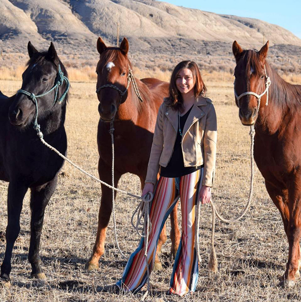 Image of Gina Valceschini standing outside with 3 horses on leashes.