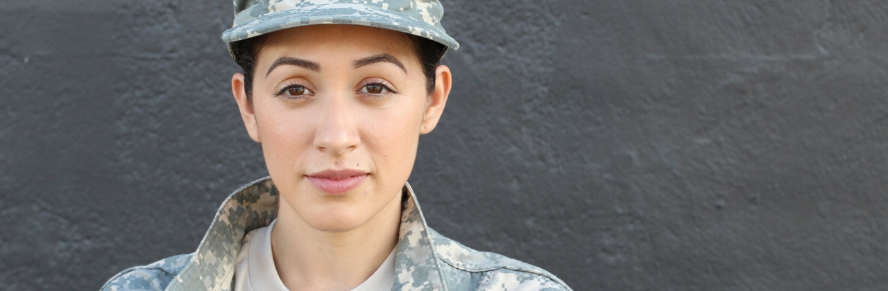 Photo of a woman in military attire looking at the camera. She is standing in front of a grey wall.