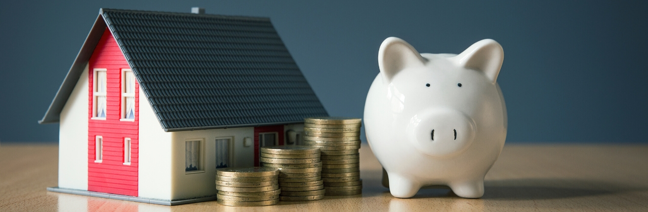 Photo of a white piggy bank next to a stack of coins and a miniature model of a house.