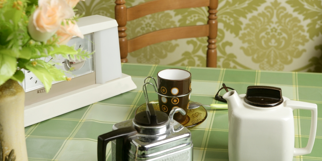Photo of a table topped with a natural green table cloth which sits in front of a wall covered with green wallpaper.