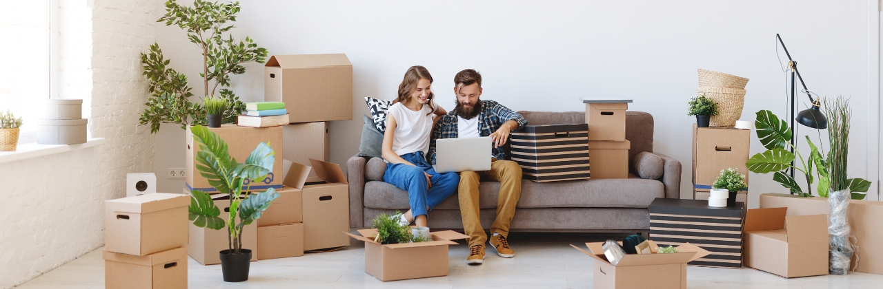 Photo of a couple sitting on the couch in the living room of their new house. All around them in the living room, are potted plants and boxes that they've not yet unpacked.