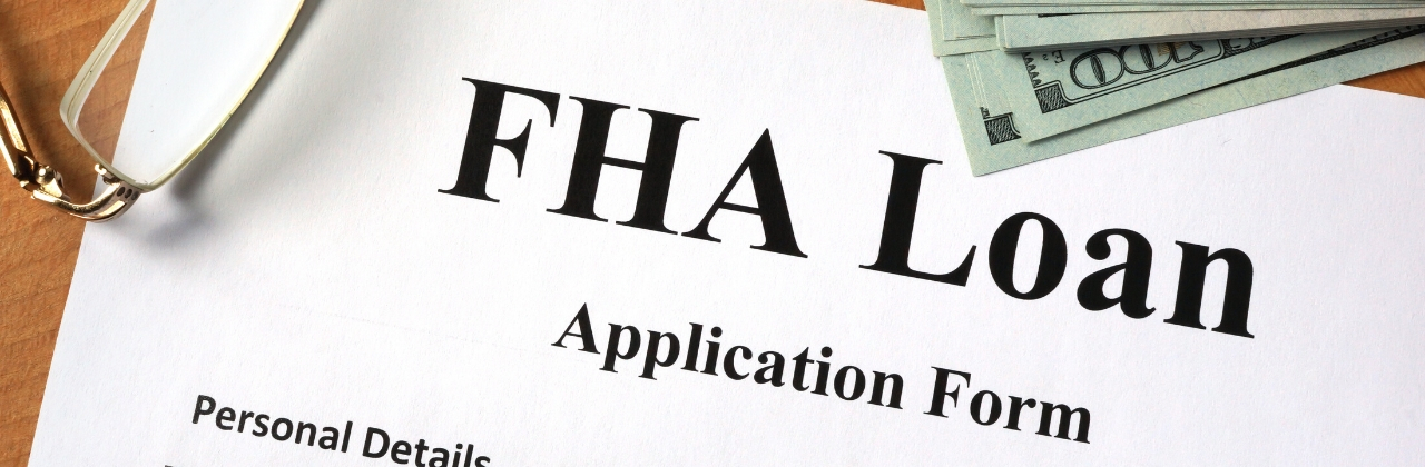 Photo of an FHA loan application with a stack of hundred dollar bills sitting next to it on a