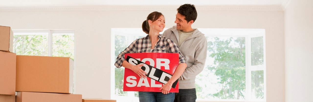 Photo of a man and woman standing in a new house filled with packed boxes. They are holding a for sale sigh with the word sold taped over it and smiling at each other.