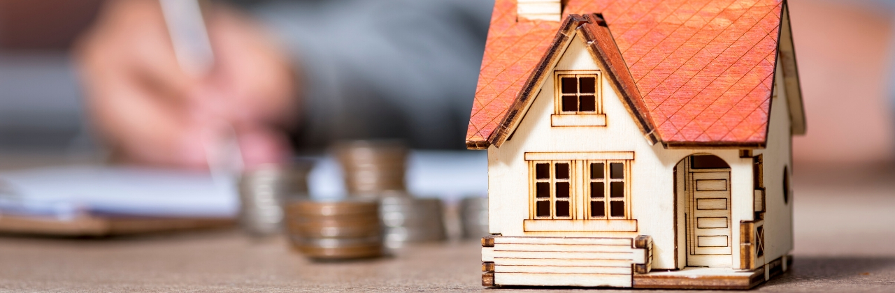 Photo of a miniature house on a desktop with a blurred man's hand in the background filling out paperwork. There are also stacks of coins that are slightly out of focus directly behind the miniature house.