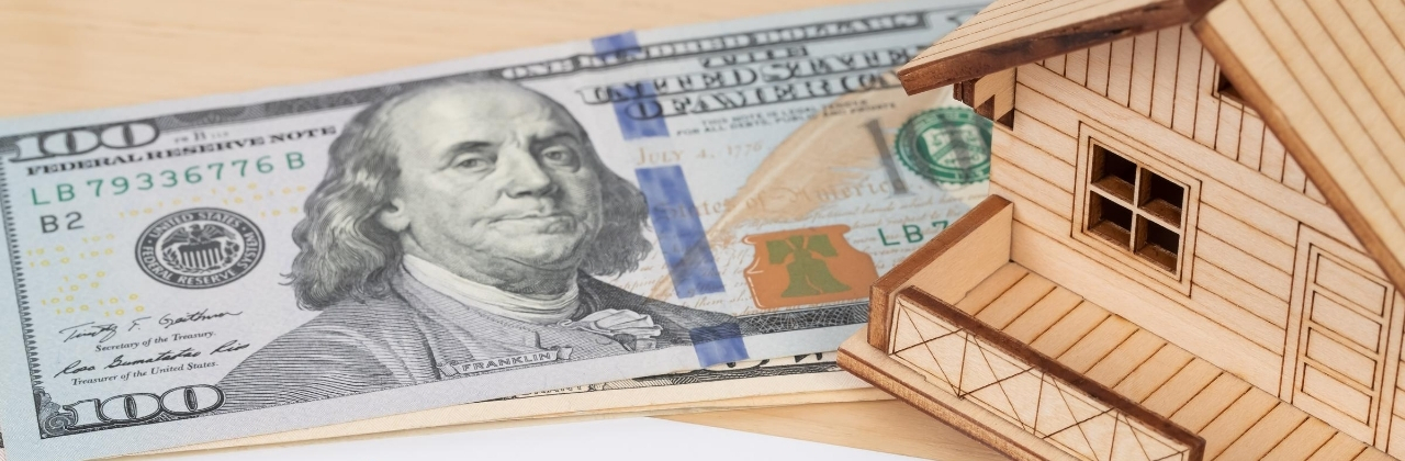 Image of a small house model and a 100 dollar bill. This image is meant to illustrate the concept of money in your pocket from your home with a reverse mortgage.