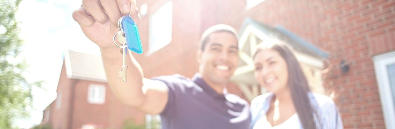 Photo of a couple standing in front of their house. The man is holding his keys out toward the camera to show he is a proud homeowner.