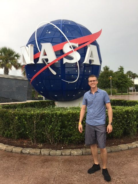 A photo of Thomas May in front of a NASA statue.
