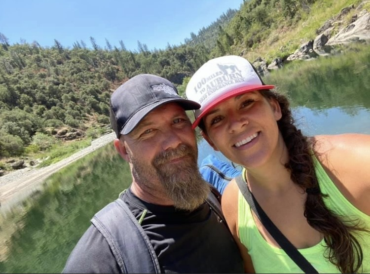A photo of Christy McCoard at the lake with her husband.