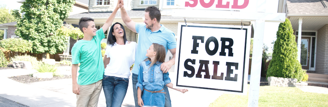 """Photo of a family standing out in front of their house next to a sign that reads """"Sold""""."""
